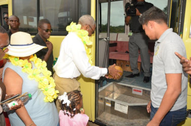 President David Granger pours coconut water to officially commission the 30-seater bus, while Minister of Social Cohesion, Amna Ally looks on. Sajid Baksh, a representative of the donor, Suresh Jagmohan is at right. (Ministry of the Presidency photo)