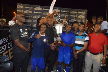 Dynasty sealed- Captain of Sparta Boss outfit Devon Millington collecting the championship trophy from Sports Director Christopher Jones while members of the team and Banks DIH Limited look on.