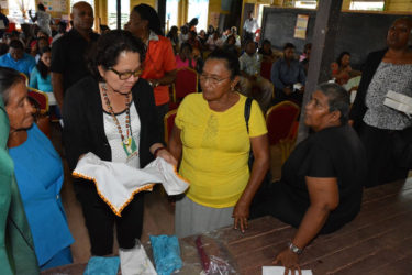 Two participants in the Self Reliance and Success in Business Workshop in Mahdia give First Lady,  Sandra Granger (centre) a closer look at their hand-embroidered tea towels.  (Ministry of the Presidency photo)