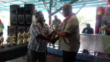 A fisherman (left) receives his award from Minister of Agriculture Noel Holder yesterday