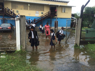 Students and a teacher with their footwear in their hands manoeuvre through the flooded school yard.