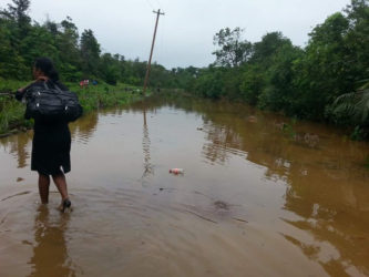 The flooded road that persons had to walk through to get to their destination.