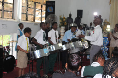 Members of the Pan Wave Steel Orchestra performing a final tribute to their colleague during the funeral service yesterday.