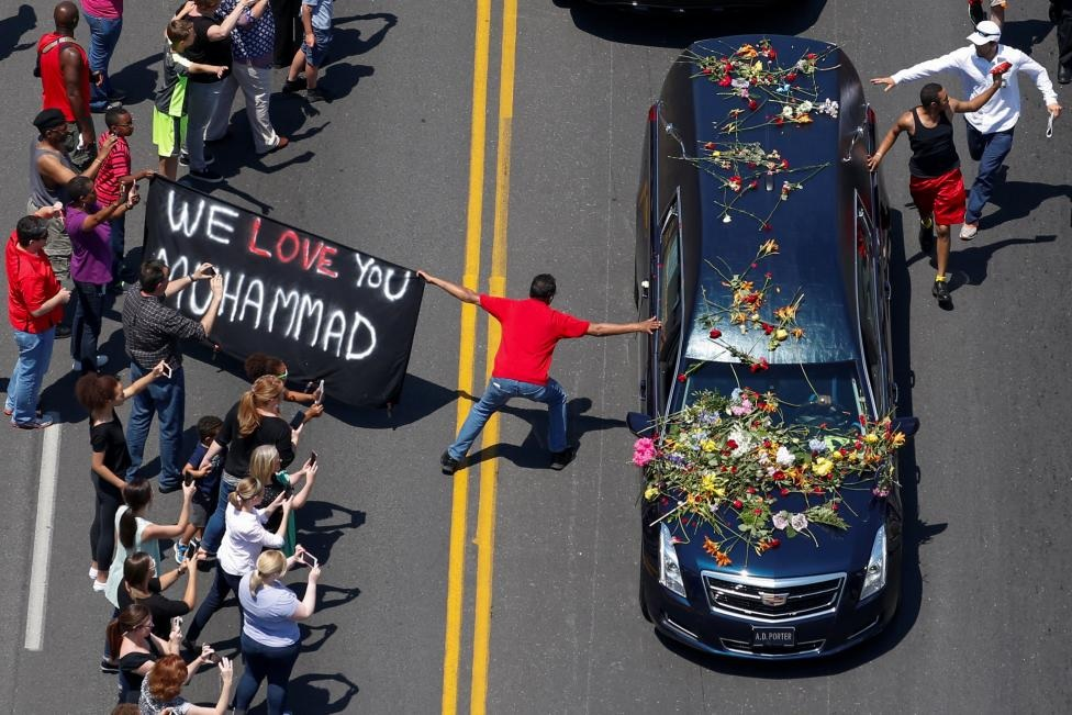 """A banner stating """"We Love You Mohammad"""" is displayed as well-wishers touch the hearse carrying the body of the late boxing champion Muhammad Ali during his funeral procession through Louisville, Kentucky, U.S., June 10, 2016. REUTERS/Adrees Latif"""