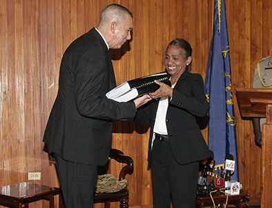President Anthony Carmona receives the report of the commission of enquiry into Clico from secretary to the commission, Judith Gonzales, at the Office of the President, St Ann's, yesterday.