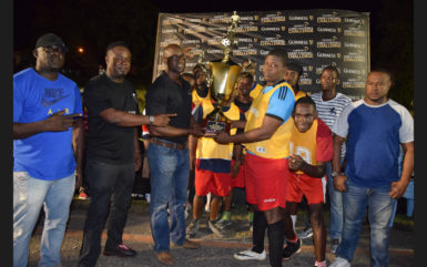 BV-B captain Erin Fraser collecting the championship trophy from Guinness Brand Manager Lee Baptiste after defeating Haslington North in the final while other members of the team and Petra Organization Co-Director Troy Mendonca (right) look on.