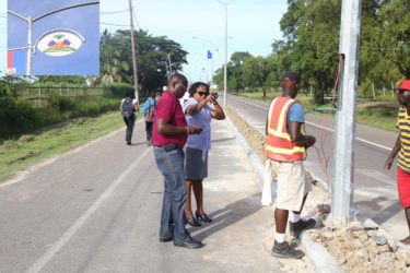 Junior Minister of Public Infrastructure Annette Ferguson yesterday inspecting works done so far on Carifesta Avenue, where the flags and courts of arms of the Caricom member states have been mounted ahead of next week's Heads of Government summit. Inset are the flag and coat of arms of Haiti. See story on page 2. (Photo by Keno George)