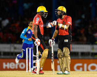 Dwayne Bravo (left) and Hashim Amla discuss strategy during their record fifth wicket stand against Barbados Trident on Friday night. (Photo courtesy CPL)
