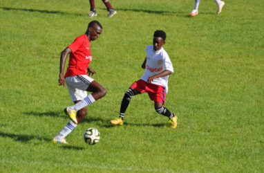 Action between Soesdyke Secondary (white) and Covent Garden in the Digicel Schools Football Championship at the Leonora Sports Facility
