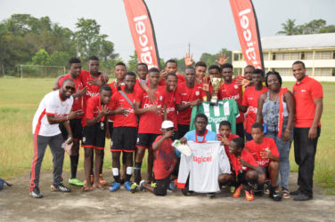 Wismar/Christianburg captain Keshawn Dey collecting the championship trophy from Digicel Representative Mario Grimshaw while other members and supporters of the team look on following their win over Kwakwani Secondary in the Region 10 Final of the Digicel Schools Football Championship