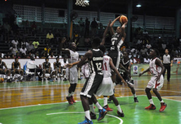 Guyana's Jordan Alphonso attempting a jump shot over several Suriname players during their team's matchup in the CBC u16 Championship at the Cliff Anderson Sports Hall.