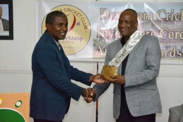 Minister of State Joseph Harmon (right) receiving a token of appreciation from President of the DCC, Alfred Mentore. (Ministry of the Presidency photo)