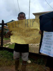 A Port Kaituma resident holding up his placard during Tuesday's protest.