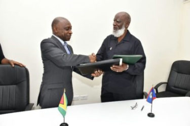 Guyana Foreign Affairs Minister, Carl Greenidge (left) exchanges a signed agreement on trade and other matters with Belize Foreign Affairs Minister, Wilfred Elrington (GINA photo)
