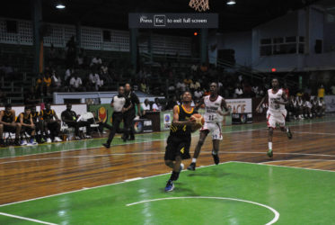 Jamaica's Jason Menzies attempting a layup while being pursued by two Trinidad and Tobago players in their CBC u16 Championship group fixture at the Cliff Anderson Sports Hall
