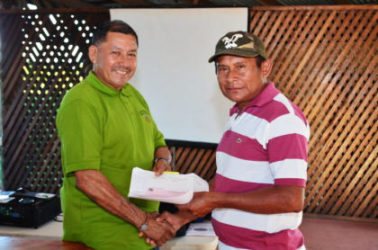 Minister of Indigenous Peoples' Affairs, Sydney Allicock (left)  handing over a cheque to a toshao of one of the beneficiary villages