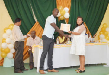 Ronald Austin of the Office of the Presidential Advisor on Youth Empowerment presents a certificate to Ulita Henry (GINA photo)