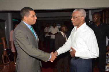 President David Granger (right) and Prime Minister Andrew Holness greeting each other at the Pegasus Hotel yesterday afternoon just before they sat down for bilateral talks. (Ministry of the Presidency photo)