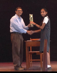 Chairman of the National Library Committee Petamber Persaud presenting an award to Sarah Dhanraj of the Bishops' High School