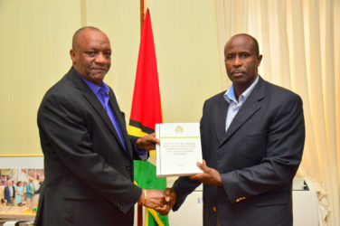 Minister of State Joseph Harmon receiving the report from Brigadier (Rtd) Bruce Lovell at the Ministry of the Presidency (Ministry of the Presidency photo)