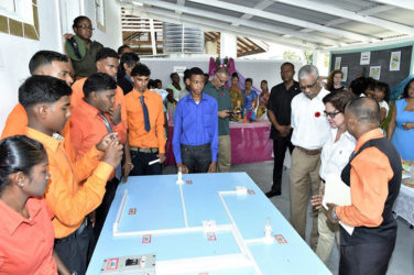 President David Granger and First Lady Sandra Granger listen as Mr. Raj, the instructor of the Electrical Installation Course, explains some of the features of the programme. (Ministry of the Presidency photo)