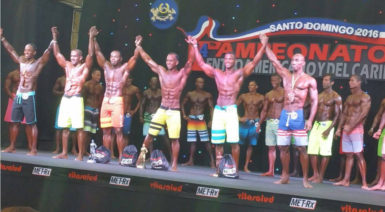 Emmerson Campbell, third from left, and the other competitor's in the Men's Physique category join hands at the conclusion of the event.