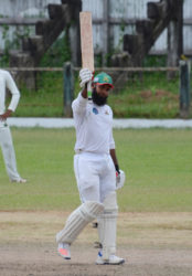 Upper Corentyne's Assad Fudadin raises his bat in acknowledgement of reaching three figures against Georgetown yesterday at Bourda. (Orlando Charles photo)