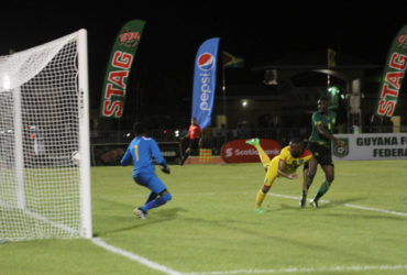 Adrian Butters of Guyana (yellow) in the process of scoring his team's second goal with a header during their match against Jamaica in the CFU Caribbean Cup Qualifiers at the National Track and Field Centre in Leonora. (Orlando Charles photo)