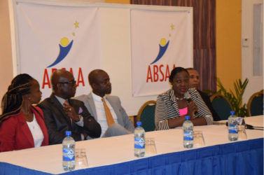 ON BOARD! Minister within the Ministry of Education Nicolette Henry addressing the gathering at the Pegasus Hotel in Kingston while members of the ABSAA including  Alex Bunbury (thirdfrom left) and NSC Chairman Ivan Persaud (left) look on.