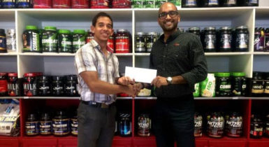 Jamie Mc Donald of Fitness Express hands over the sponsorship contribution  to Navin Singh of the Guyana Amateur Powerlifting Federation.