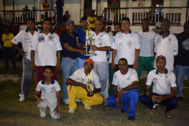 The victorious Floodlights team with skipper Ricky Deonarine receiving the trophy.