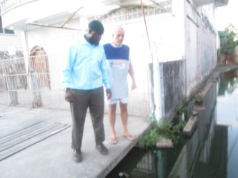 Joseph Ramsey (at right right) shows City Engineer Rasheed Kellman the water which inundates his entrance.