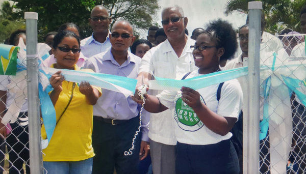Minister Noel Holder being assisted to cut the ribbon to commission the Hydromet Service's Climatological Station at the Guyana School of Agriculture. (Shabna Rahman photo)