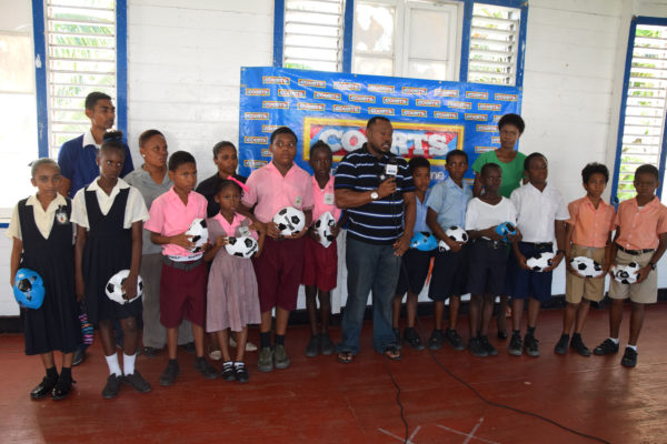 Students of the participating schools in the 5th Annual Courts Pee Wee Football Championship displaying their donated footballs from the Petra Organization while Co-Director Troy Mendonca (centre) of the aforesaid entity addresses the media gathering.