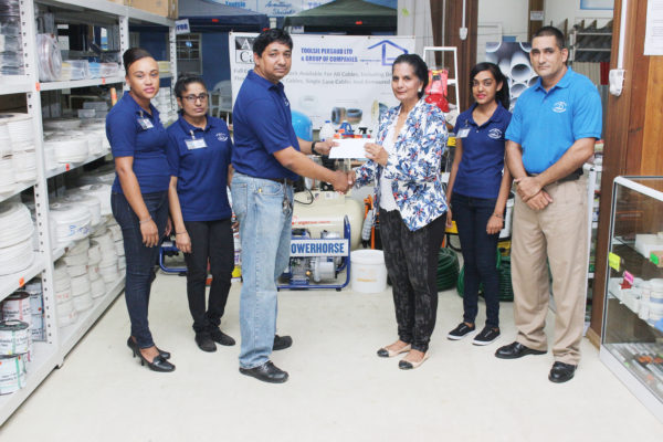 General Manager of Toolsie Persaud Ltd Ray Sukhnandan hands over a cheque to Deborah Ramotar-Skeete, the Administrative Coordinator of the Guyana Book Foundation to aid in its literacy programmes. (Photo by Keno George)