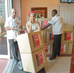 In photo, Miss World Guyana Nuriyyih Gerrard & John Lewis Styles (JLS) Staff assist in loading the boxes for delivery. (JLS photo)