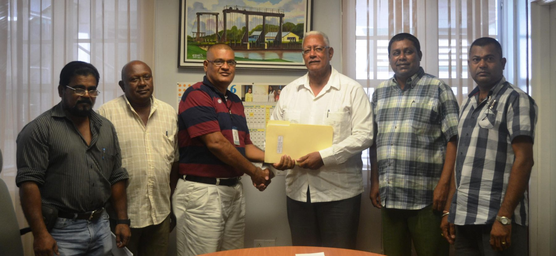 Agriculture Minister Noel Holder (third from right) receiving the plan from Gobin Harbhajan, the Prime Minister's representative. (Ministry of Agriculture photo)