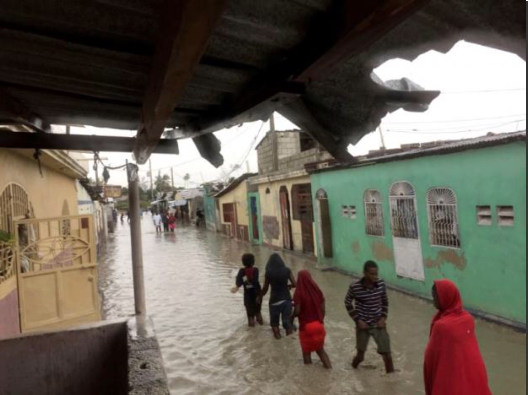 People wade through a flooded street while Hurricane Matthew passes, in Cite-Soleil in Port-au-Prince, Haiti, October 4, 2016. REUTERS/Carlos Garcia Rawlins
