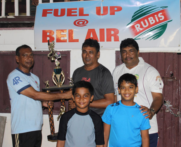 At left, Ramesh Sunich of  the Trophy Stall hands over the winning trophy to Anil Persaud of the East Coast Cricket Committee in the presence of two under 15 players and Guyana Floodlight Softball Cricket Association representative Anil Beharry.