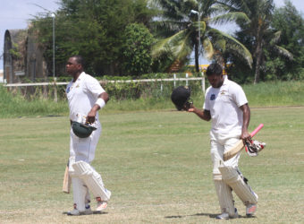 With the armouries in the background, the big 'guns' of Christoper Barnwell (143) and Chandrapaul Hemraj (79), head to lunch yesterday on the final day of the GCB's  practice match at the Everest Cricket Ground. (Photo by Orlando Charles)