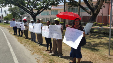 Eleven Demerara Timbers Limited (DTL) workers, who were sacked for protesting in front of the company's head office last month, yesterday protested outside of the Ministry of the Presidency in hopes of securing President David Granger's intervention in the case.