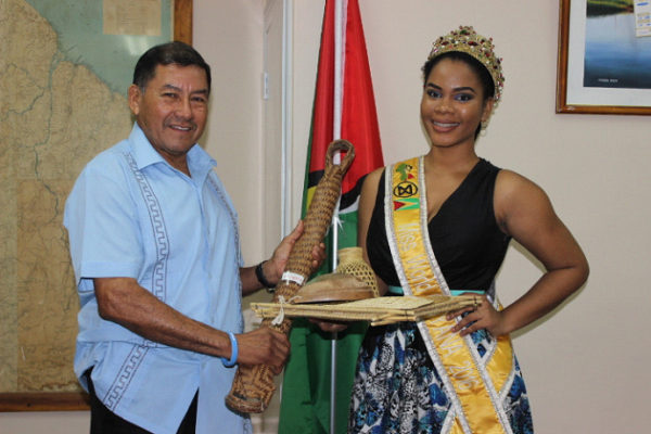 Minister of Indigenous Peoples Affairs Sydney Allicock presenting the Indigenous craft to Miss World Guyana Nuriyyih Gerard.