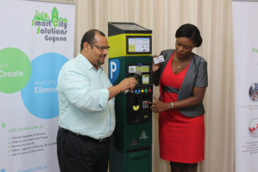 Smart City Solutions Accounting Manager Alicia Bess and a colleague demonstrate how the parking meters work.