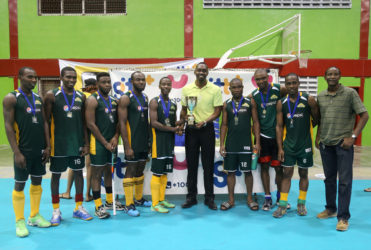 Hikers 1st Division Captain Robert France (centre) collecting the championship trophy from Director of Sports Christopher Jones after defeating Bounty GCC in the GTT National Indoor Hockey Tournament final.