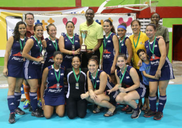Director of Sports Christopher Jones handing over the Women's Championship trophy to Bounty GCC captain Tiffany Solomon following the conclusion of the GTT National Indoor Hockey Tournament (See page 27)