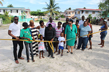 Minister within the Ministry of Education Nicolette Henry (third, right in front), Georgetown Mayor Patricia Chase-Green (second, right) and Director of Sport Christopher Jones (far left) flanked by residents of Guyhoc Park as the ribbon is cut for official commissioning yesterday. (Photo by Keno George)
