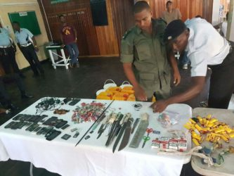 Joint Services members going through the contraband seized yesterday morning at the Georgetown Prison. (Ministry of the Presidency photo)