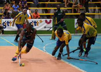 Hikers Aroydy Branford (green) trying to maintain possession of the ball amid the pressure from several players of the National Junior Men's Team during their first division semi-final at the National Gymnasium  Saturday.