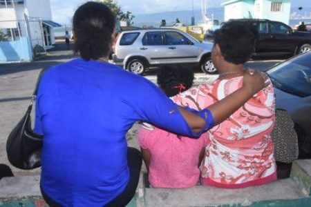 Family members wait for answers outside the Port Royal Police Station following last December's fatal accident off Maiden Cay in Kingston, Jamaica.