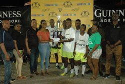 Still champs! Banks DIH Berbice representative Renesha Gilford presents the championship trophy and cash prize to Trafalgar Captain Adrian Price in the presence of Guinness Brand Manager Lee Baptiste (right), teammates and other officials following the end of the event.